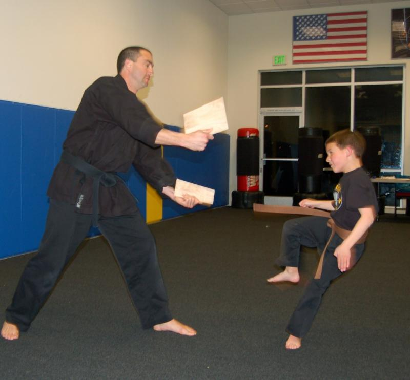 Simon breaks about board at his martial arts class.