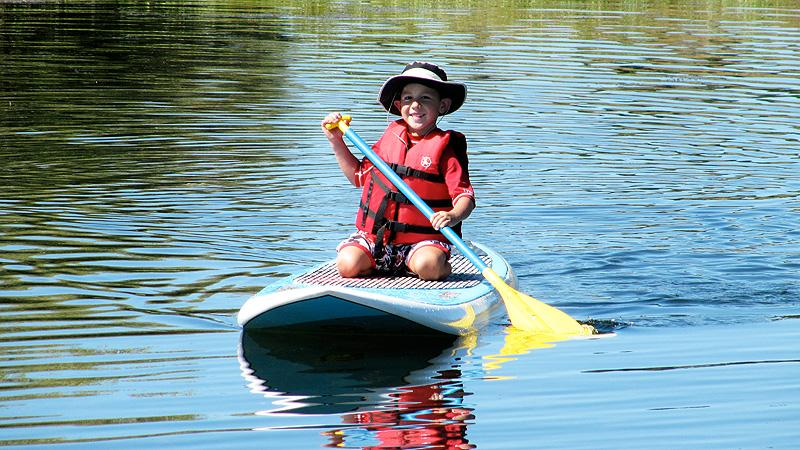 Henry tries out a standup paddleboard, not quite standing up.